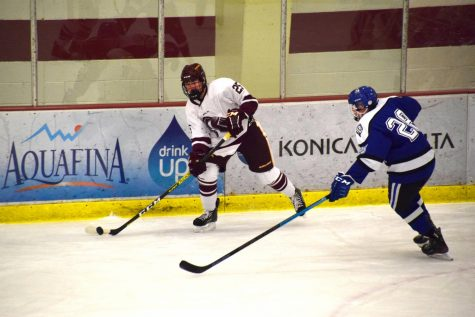 Matthew Rockwell (9) is the only CHHS athlete apart of the Irondale-St. Anthony cooperative hockey program. Here, he looks to pass during a game against Woodbury.
