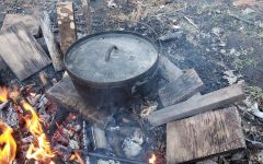 The dutch oven is prepped for cooking atop several coals.
