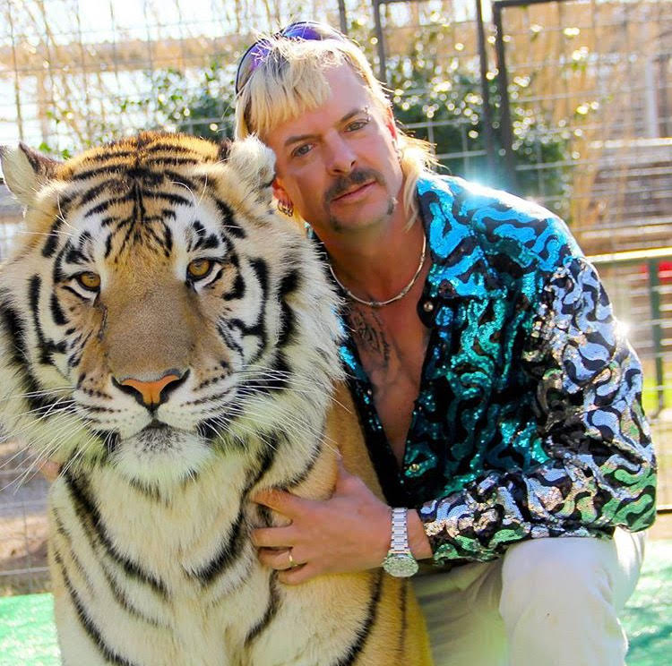 Unpredictable+%22Joe+Exotic%22+poses+with+a+large+tiger.