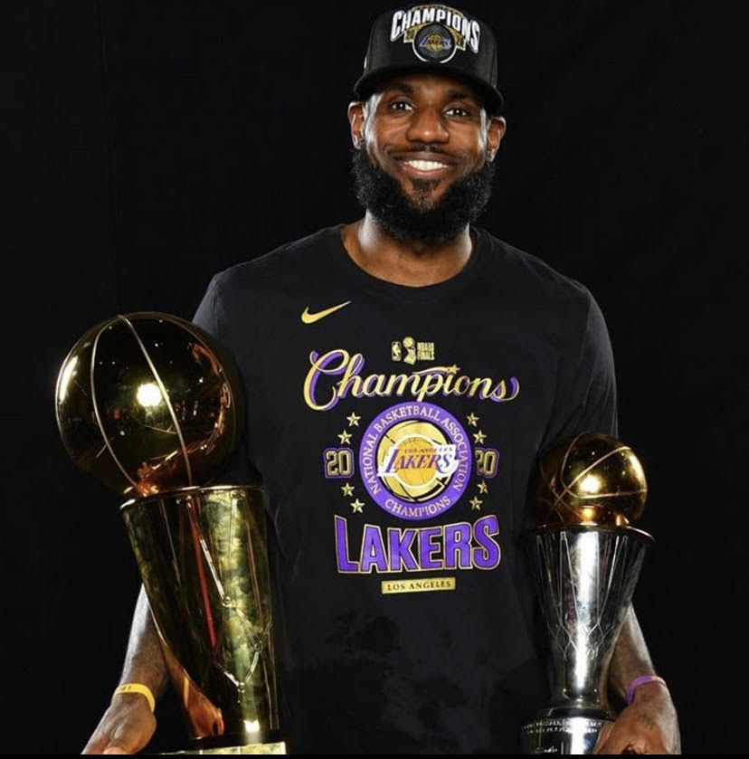 Finals MVP Lebron James holds the Larry O' Brien finals trophy as well as the Bill Russel finals MVP trophy.