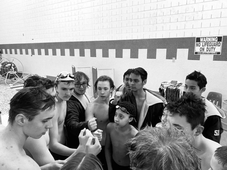 The boys' swim team huddle up for a break.