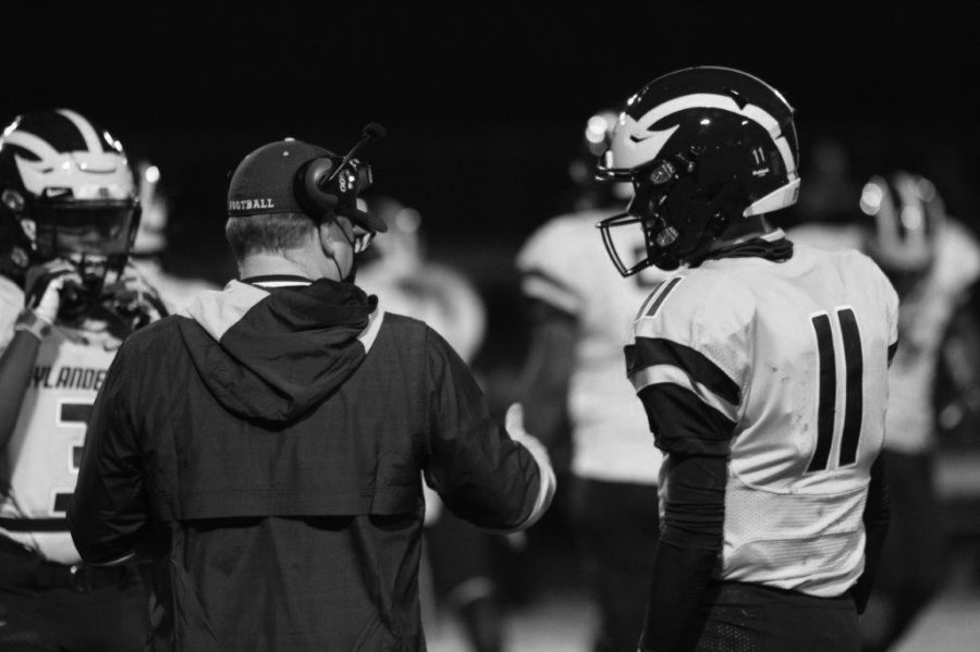 Coach Matt Townsend confers with a player on the sidelines.