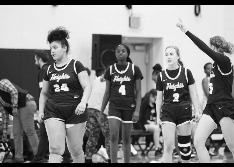 Sakhia Howard-Reynolds (12) and her teammates step onto the court.
