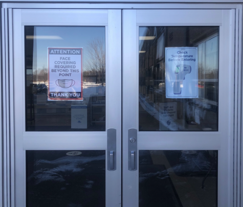 The doors to Columbia Heights High School remain plastered with info-graphic posters while staff plans for their vaccination.