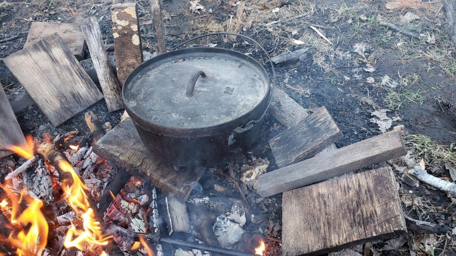 The+dutch+oven+is+prepped+for+cooking+atop+several+coals.
