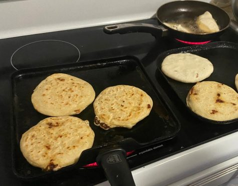 The golden pupusas are flipped on the stove.