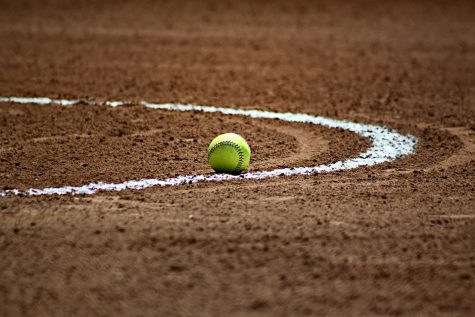 A softball lays on its field, untouched.
