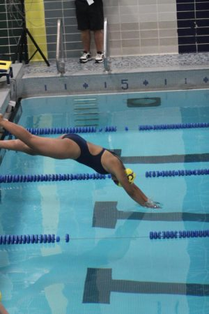 Marissa Foy (10) dives into the pool after removing her facemask.